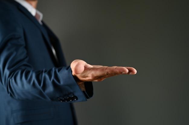 スーツを着た男が手のひらを差し出す