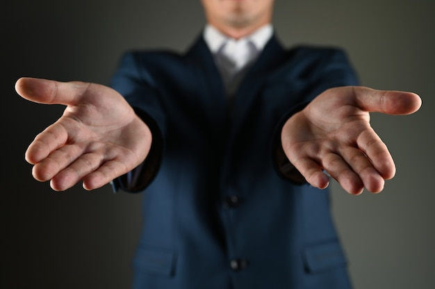 양복 입은 남자는 손바닥을 앞으로 뻗는다. 고품질 사진