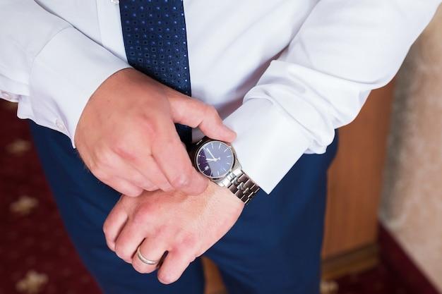 Мужчина в белой рубашке и синем галстуке носит часы.