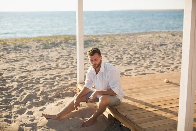 Мужчина в белой рубашке и шортах сидит на пляже