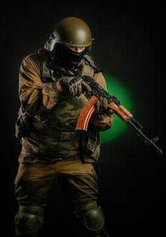 Мужчина в форме с ружьем позирует, прицеливание, перезарядка, стрельба, на темном фоне в студии