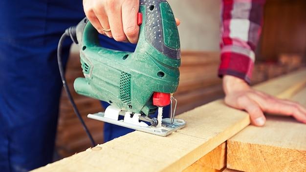 Человек режет деревянную доску с помощью головоломки