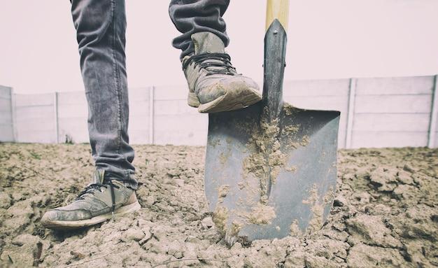 남자는 시골집에서 흙을 파고 있다