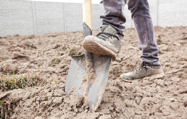 男は田舎の家の土を掘っている