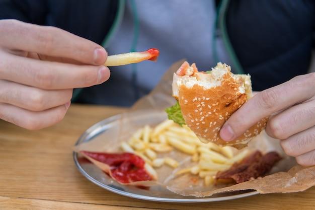 그 남자는 패스트푸드 거리 식당에서 햄버거를 먹고 있다. 케첩을 곁들인 감자튀김 한 조각.