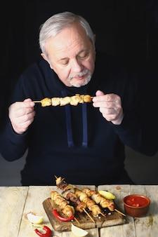 男は鶏の串焼きを食べています