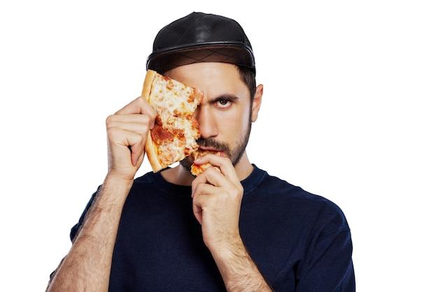 男はピザのスライスを食べています。あごひげと帽子をかぶった若いブルネット。食欲をそそるスナック。閉じる。白い背景で隔離。テキスト用のスペース。