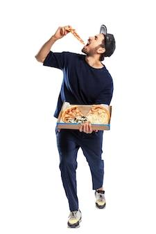 男はピザのスライスを食べています。あごひげと帽子をかぶった若いブルネット。食欲をそそるスナックをお届けします。白い背景で隔離。垂直。フルハイト。
