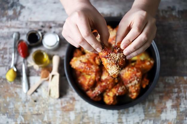 남자가 닭 날개를 먹고있다. 닭 날개 튀김.