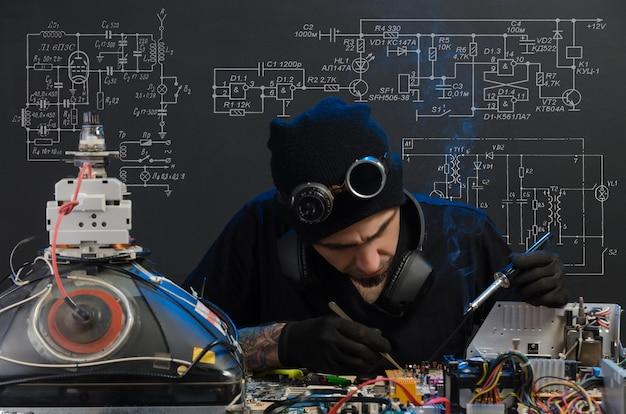 남자는 전자 제품 수리에 종사하고 있습니다.