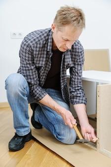 Мужчина вбивает деревянную булавку в мебельную доску.