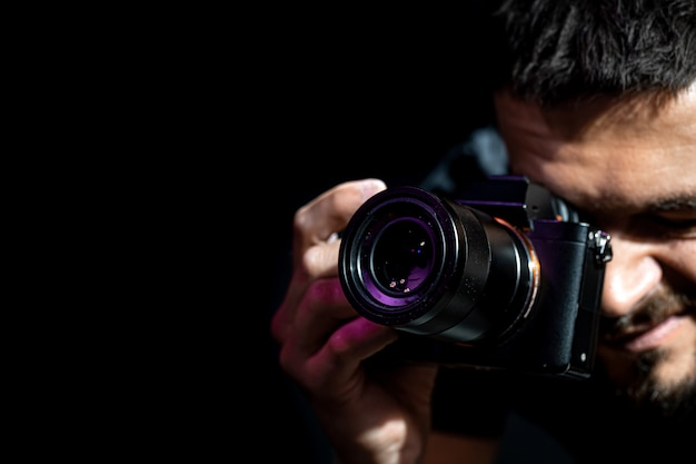 Мужчина держит фотоаппарат и готовится к съемке. фотограф смотрит в видоискатель камеры и делает снимки.