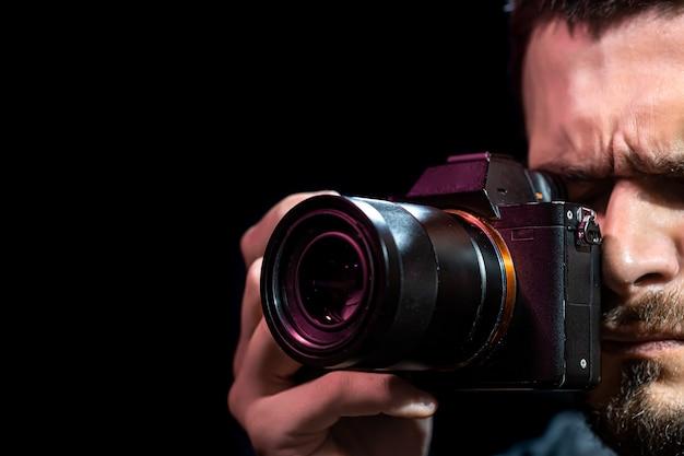 Мужчина держит фотоаппарат и готовится к съемке.