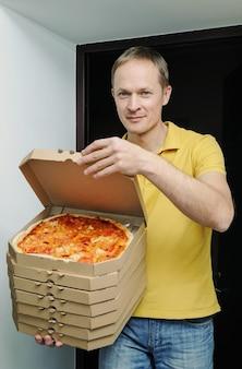 男は戸口にピザの入った箱を持っています