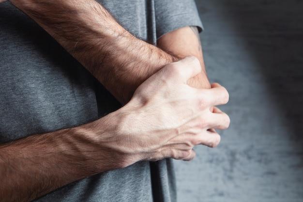 남자가 손을 잡고 있어요. 팔꿈치 통증