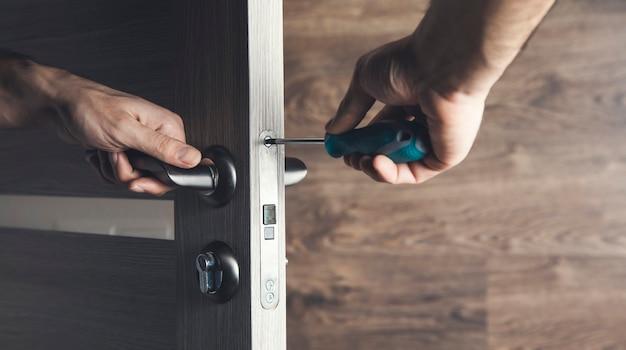 男はドライバーで木製のドアの一部を取り付けています