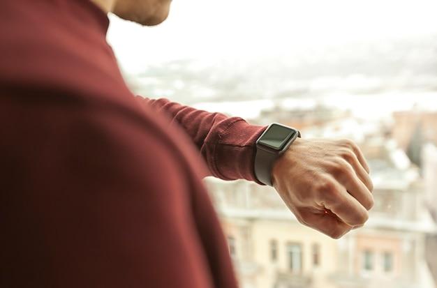 男は都市の景色を望む窓の前で彼の手に彼のスマートな時計を見ています