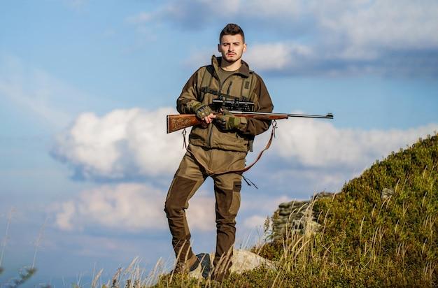 Мужчина на охоте. охотничье ружье. охотник с охотничьим ружьем и охотничьей формой для охоты на фоне неба. охотник целится. человек-охотник. прицеливание стрелка в цель. период охоты.