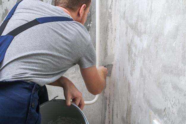 男は部屋の壁を漆喰で塗っている。閉じる。