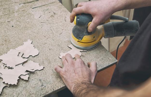 男は研磨機で木を加工している