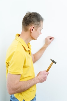 남자는 그림을 걸기 위해 벽에 못을 박고있다.