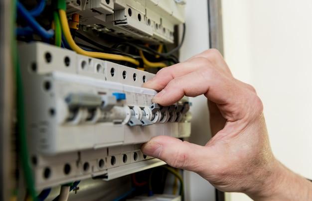 Мужчина ремонтирует напряжение распределительного щита с помощью автоматических выключателей.