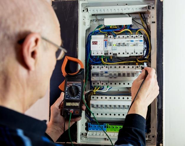 男は自動スイッチで配電盤の電圧を修理しています。