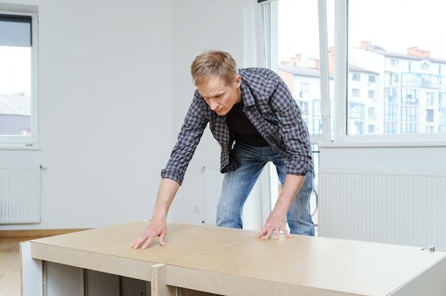 Человек устанавливает панель мдф в задней части комода.