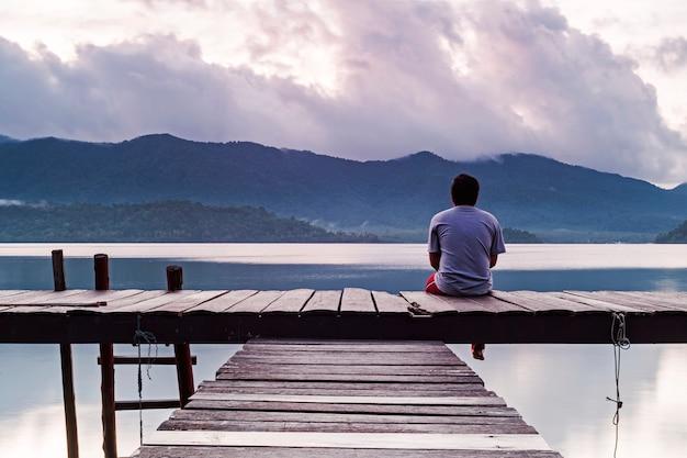 その男は、早朝の風景を背負って孤独な感情に座っています。