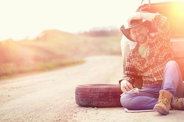 男は自然の中で車のそばの道路に座っています