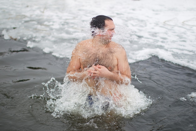 男は氷の穴で泳いでいます。