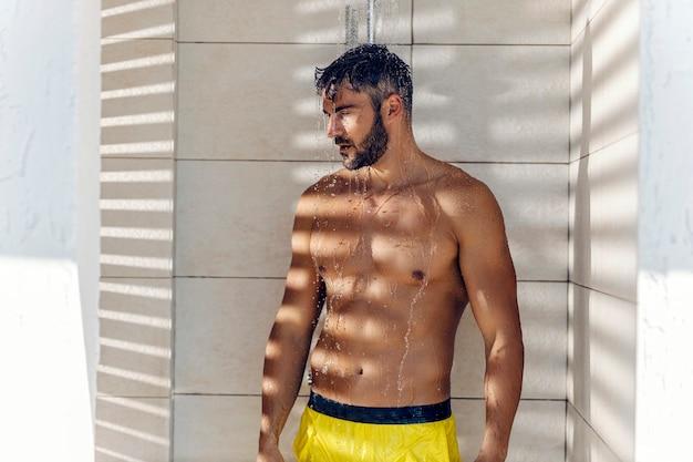 Мужчина принимает душ. красивый высокий мускулистый мужчина принимает душ после купания. полуобнаженный мужчина в желтых купальных шортах стоит в салоне и моет волосы.