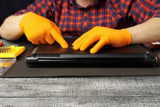 남자가 노트북을 분해합니다. 컴퓨터 서비스 및 수리 개념. 수리점에서 노트북을 분해, 클로즈업.