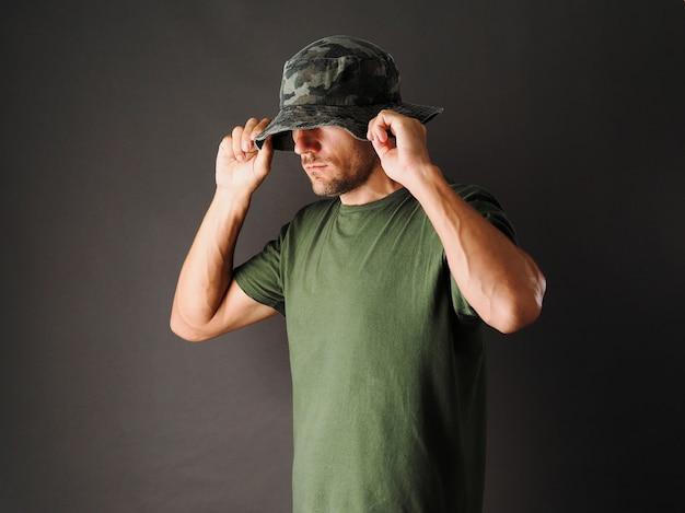 男は灰色に緑のカモフラージュパナマハットと緑のtシャツを着ています。