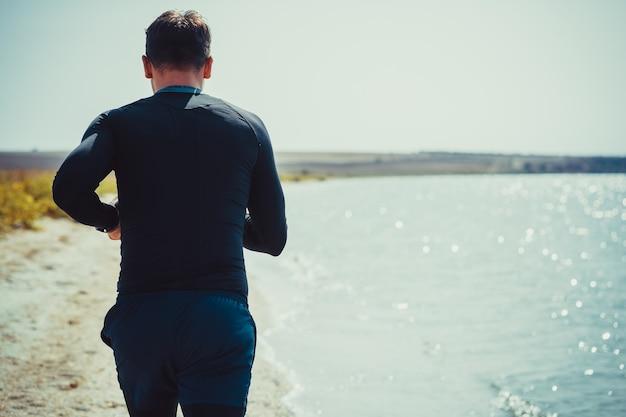 海岸沿いをジョギングしている男