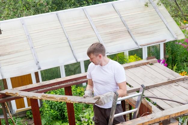 男は屋根の解析からハンマーで古い腐った木の板をノックします