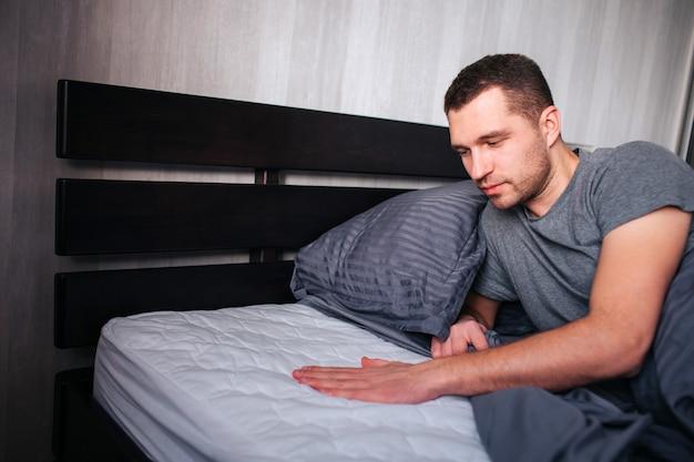 남자는 침대용 새 매트리스에 누워 구매에 만족합니다