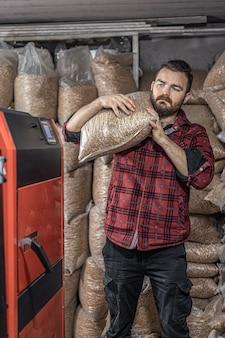 Мужчина загружает пеллеты в твердотопливный котел, работающий на биотопливе.
