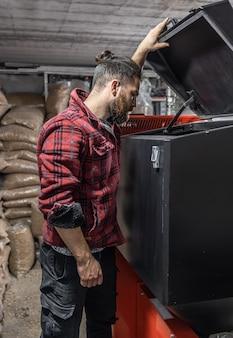 Мужчина смотрит в котел на твердом топливе в комнате с пеллетами