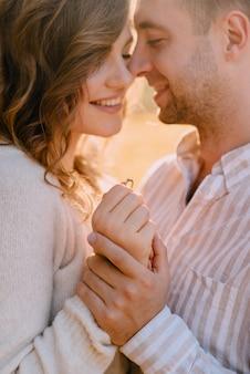 男はガールフレンドに申し出をし、彼女はそう言った。手に結婚指輪のクローズアップ。