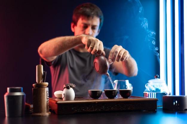 한 남자가 중국 전통 전통에 따라 기구로 차 탁자에서 차를 만들고 있다