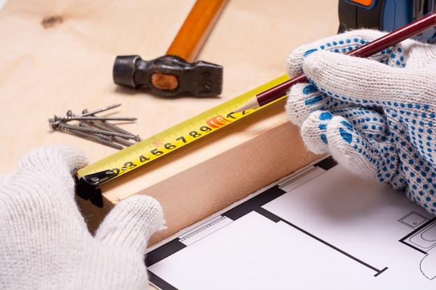 Человек измеряет расстояние на доске. рабочие инструменты с проектами домов