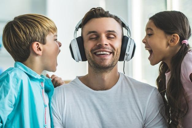 Мужчина возле детей, слушающих музыку в наушниках