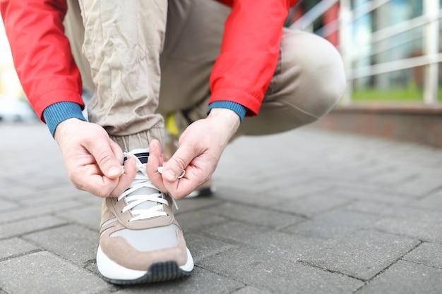 Человек на улице наклонился, чтобы завязать шнурки на ботинках. парень в городе поправляет обувь