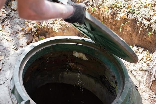Мужчина открывает люк канализации. осмотр и обслуживание септиков.