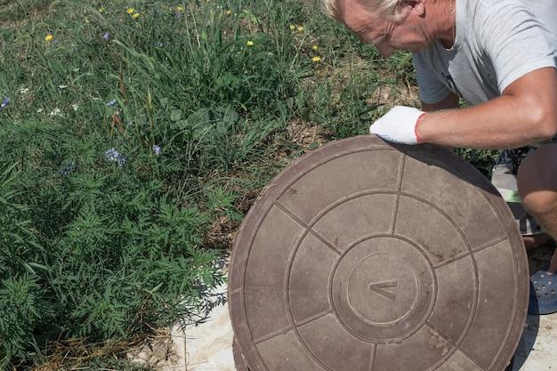 남자는 우물의 맨홀 뚜껑을 엽니다. 수도 계량 점검 및 수정.