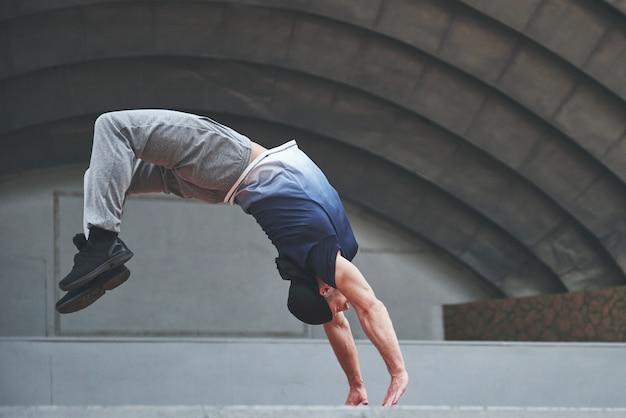 Мужчина на природе занимается паркуром, экстремальной акробатикой.