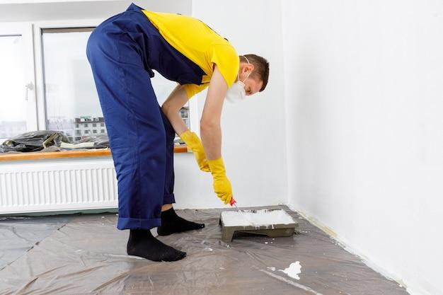 男は壁と天井を白い色で塗ります部屋の塗装と修理。
