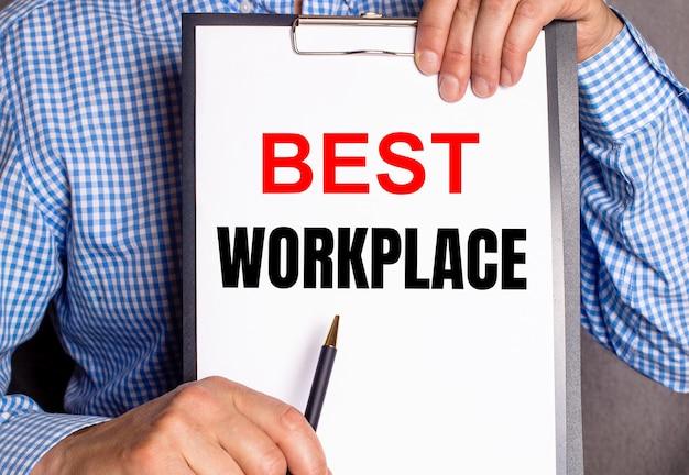 남자는 펜으로 흰색 시트의 best workplace 텍스트를 가리 킵니다.