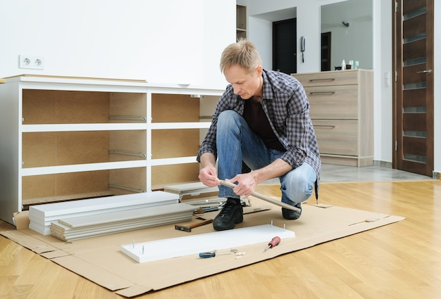 木製のピンを家具板に押し込む男
